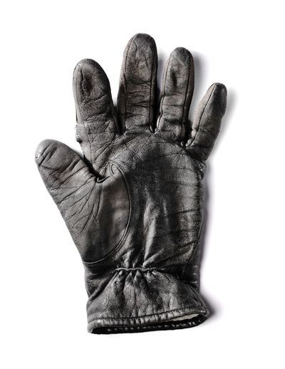 Old worn black leather glove isolated on white with natural shadow.