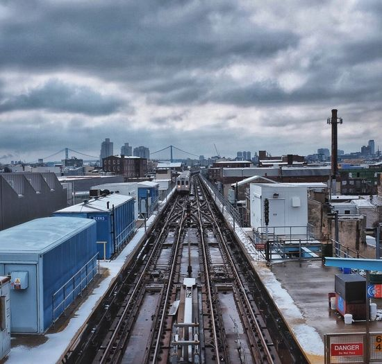 Train Tracks In City AGAINST CLOUDY SKY