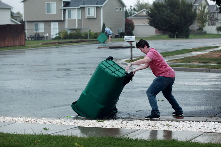 Woman flipping garbage can on street