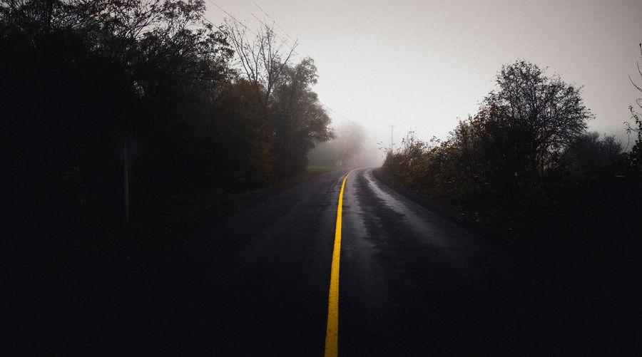 Road amidst trees during rainy season
