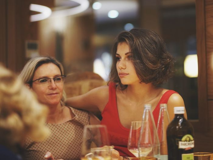 Mother and daughter looking away while sitting at restaurant