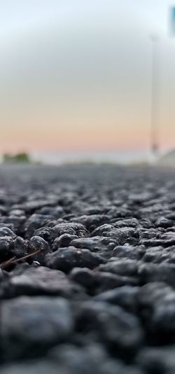 Surface level of rocks at beach against sky