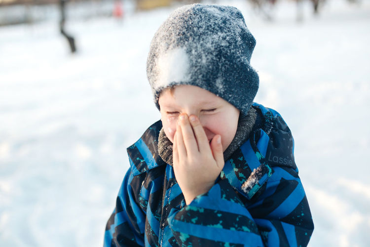 Close-up of smiling boy in snow outdoors