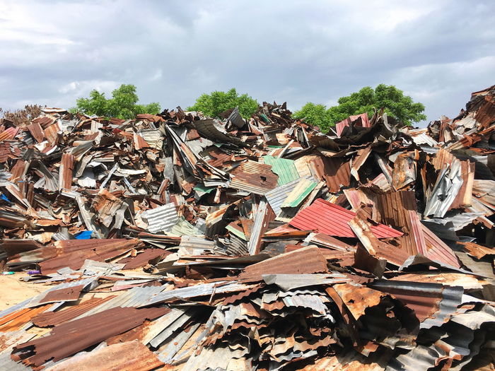 Heap Of Scrap Metals Against Cloudy Sky At Garbage Dump