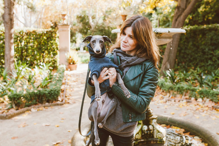 Smiling woman with dog standing outdoors