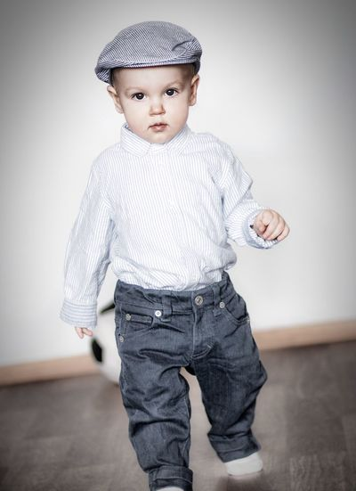 Portrait Of Boy Wearing Flat Cap Walking Against Wall At Home