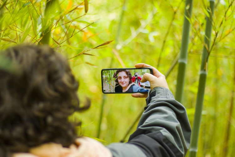 Woman takes self photo, mobile phone and nature background
