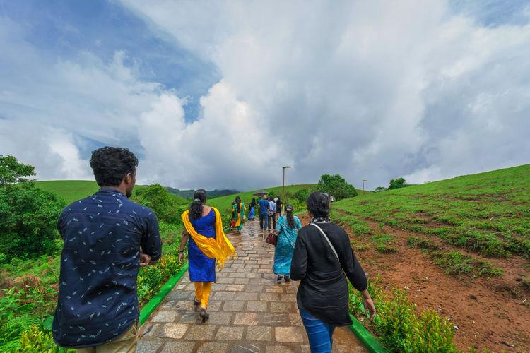 Rear view of people walking on road against sky