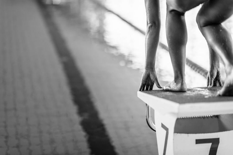 Low section of woman standing on block in swimming pool