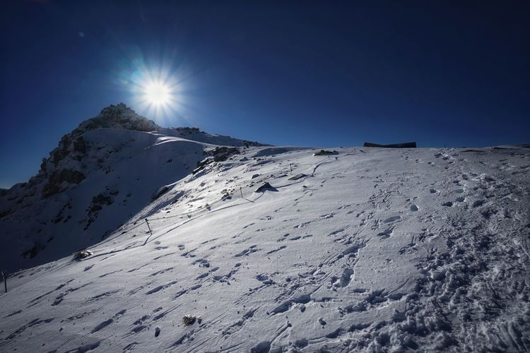 Scenic view of snow covered mountains against bright sun