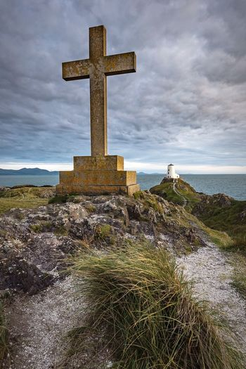 Cross on rocky shore against cloudy sky