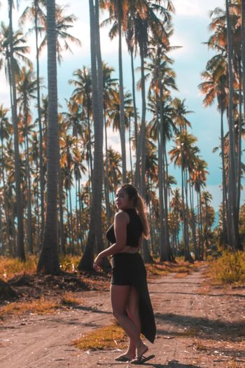Portrait Of Young Woman Standing On Dirt Road Against Palm Trees