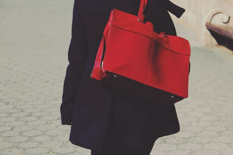 Midsection of woman with red shoulder bag standing on street