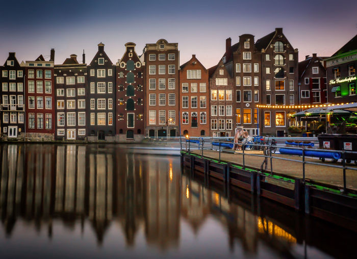 Canal by buildings at dusk
