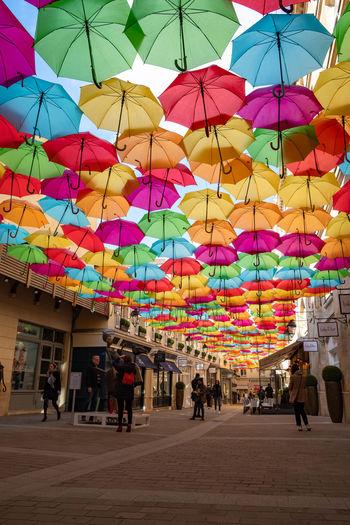 People walking on multi colored umbrellas in city