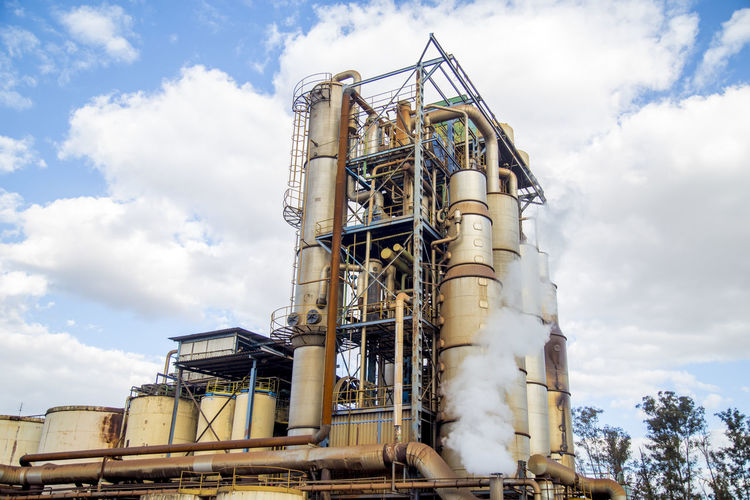 Destillery Alcohol Architecture Building Exterior Built Structure Cloud - Sky Day Factory Fuel And Power Generation Industrial Building  Industrial Equipment Industry Ladder Low Angle View Metal Nature No People Oil Industry Outdoors Pipe - Tube Refinery Sky Sugar Cane Technology