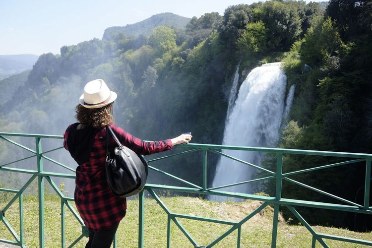 The girl admires Marmore waterfalls Looking At View Outdoors Lifestyles Clothing Hat One Person Real People Nature Adult Day Woman From Behind Marmore Waterfall Park Tourist Travel Destinations