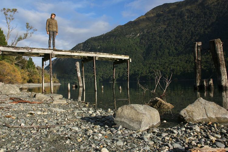 Man Standing On Pier Over Lake Against Mountain