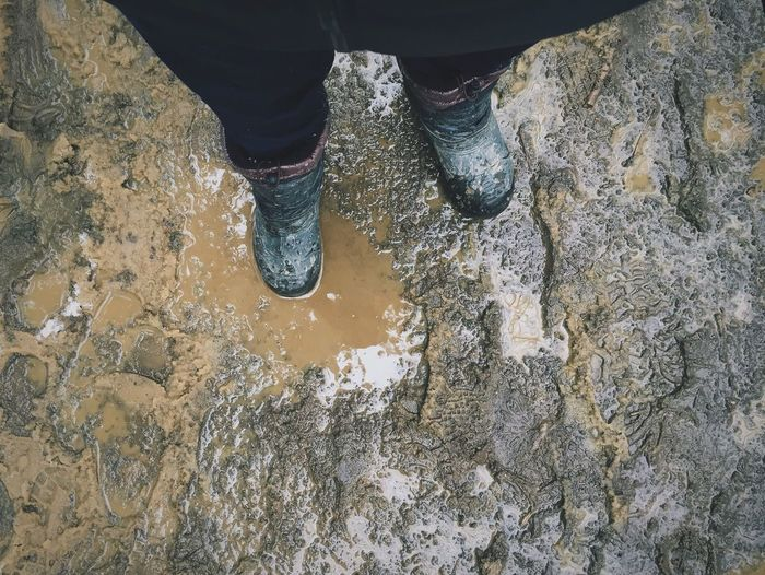 Low Section Of Man Wearing Gumboots In Mud
