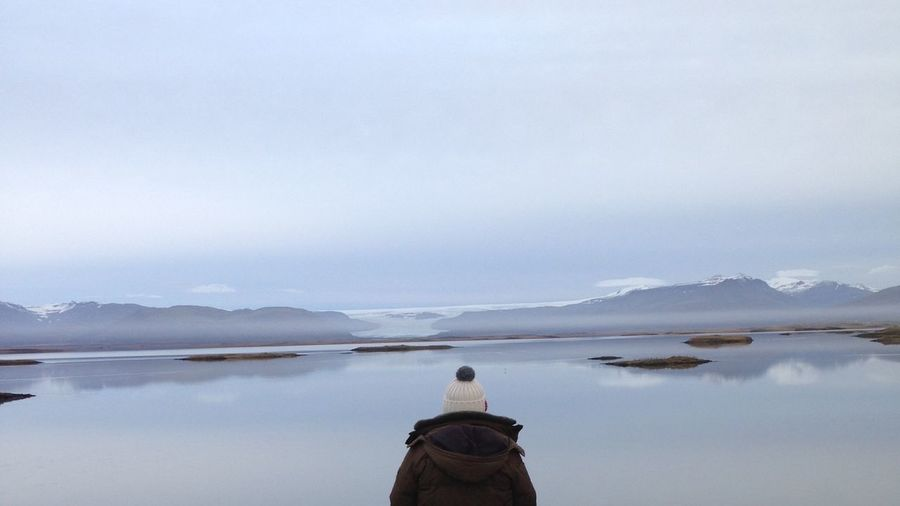 Rear View Of Person Standing By Lake Against Sky During Winter