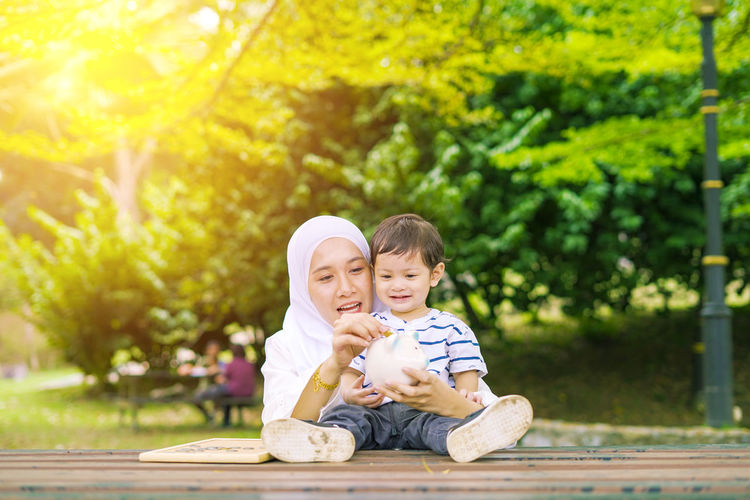 Young woman with her cute son learn how to put coins into piggy bank. Future planning concept. Child Childhood Togetherness Family Males  Men Bonding Son Innocence Two People Boys Sitting Emotion Offspring Happiness Tree Portrait Smiling Casual Clothing Plant Day Positive Emotion Sister