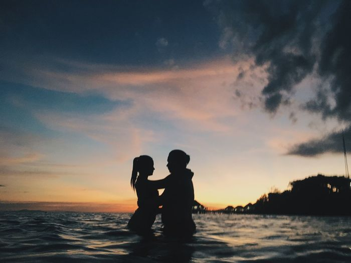 Silhouette couple standing by sea against sky during sunset