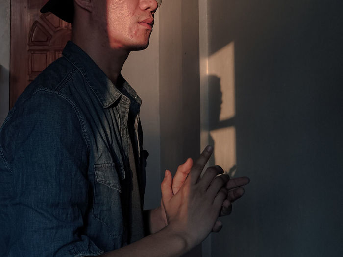 Midsection of man standing against wall at home