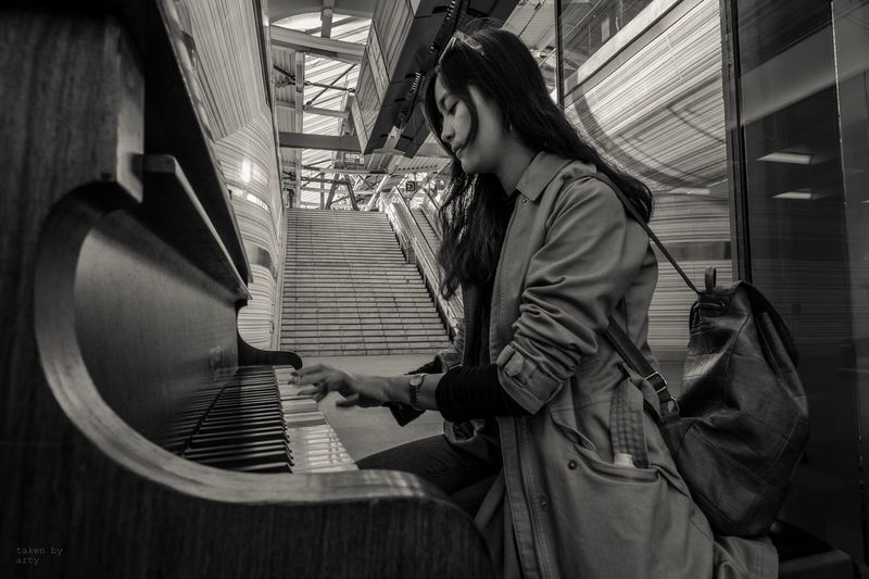 Young woman playing piano in building