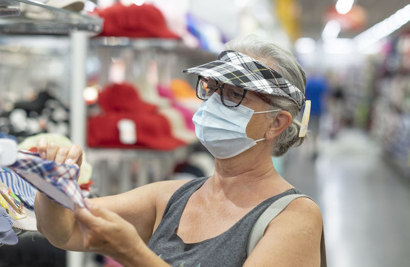Senior woman with mask shopping