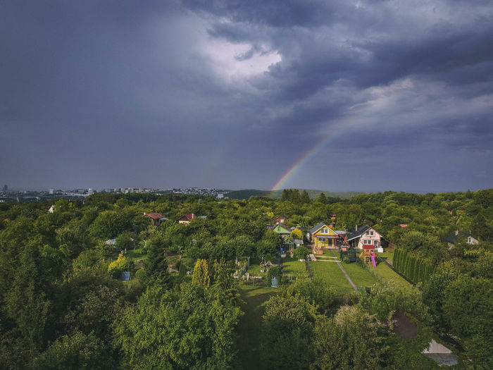 Scenic view of rainbow over trees and houses against sky