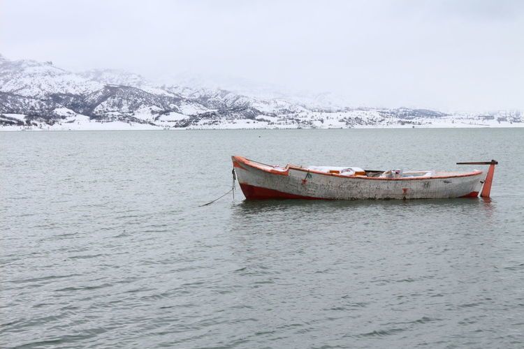 Boat in sea against sky during winter