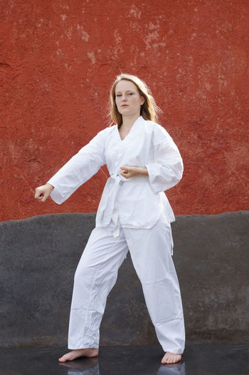 Full Length Portrait Of Woman Practicing Karate Against Red Wall