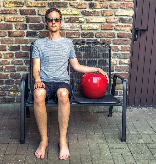 Man sitting on a bench besides a giant apple Apple - Fruit Apple One Person Looking At Camera Portrait Front View Brick Casual Clothing Glasses One Person Looking At Camera Portrait Front View Brick Casual Clothing Glasses Adult Men Lifestyles Young Adult Brick Wall Sitting Young Men Shorts Real People Wall Sunglasses Fashion Full Length