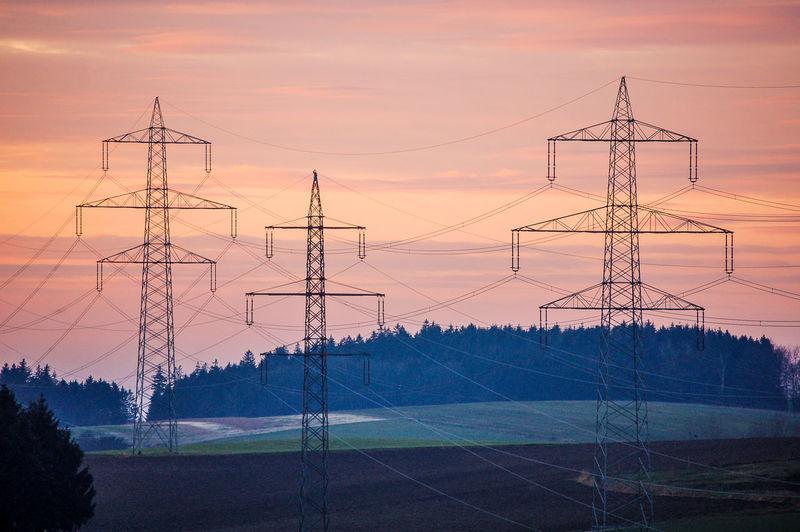 Electricity Pylon On Landscape Against Sky At Sunset
