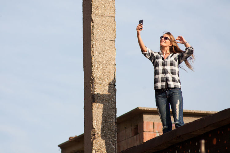 Low angle view of smiling woman talking selfie on terrace