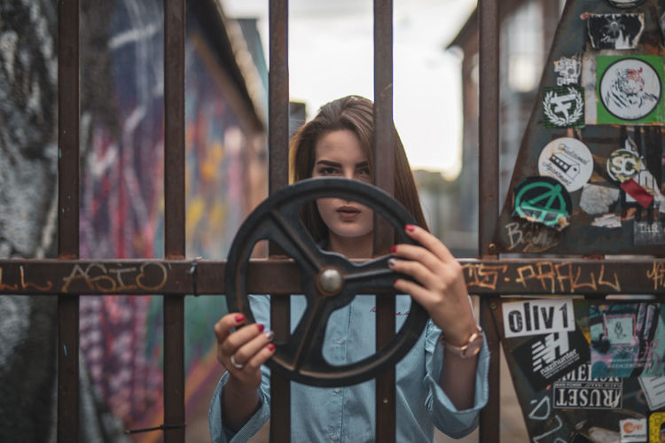 Portrait of young woman holding steering wheel while standing by metallic gate