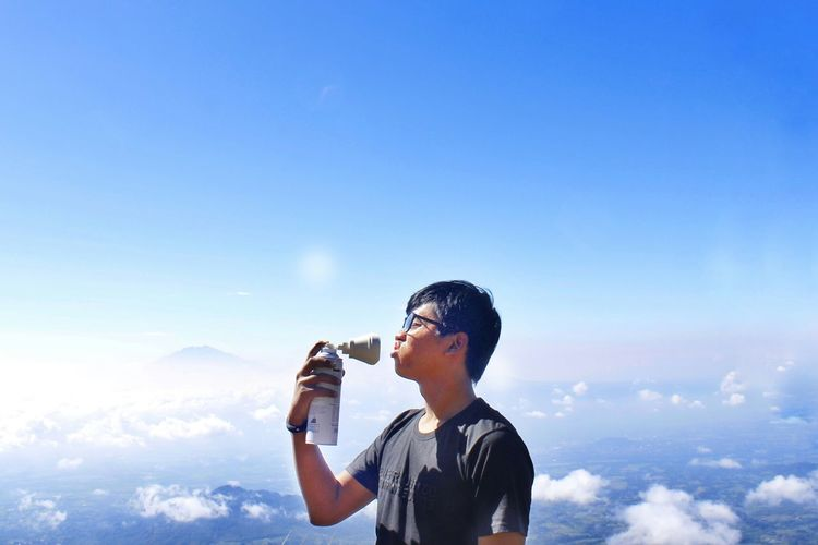 Young man making face while holding drink bottle on mountain against sky