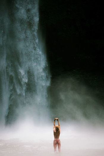 Rear view of woman in bikini standing against waterfall