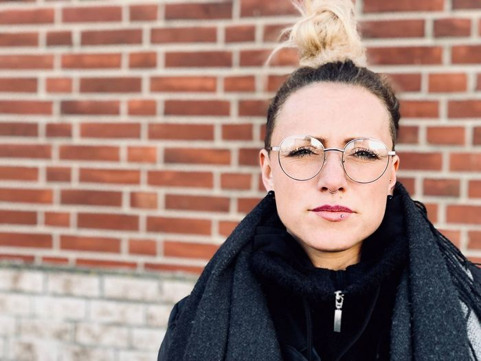 Portrait Of Young Woman Wearing Eyeglasses Against Brick Wall
