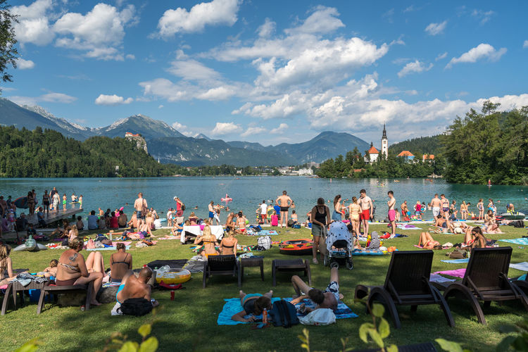 People enjoying at lakeshore against sky