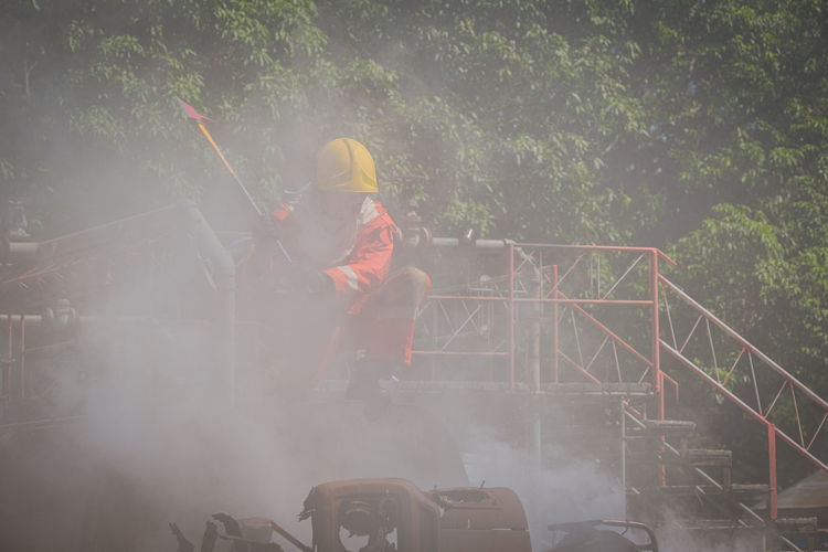 Firefighter with work tool looking at smoke while crouching at footbridge