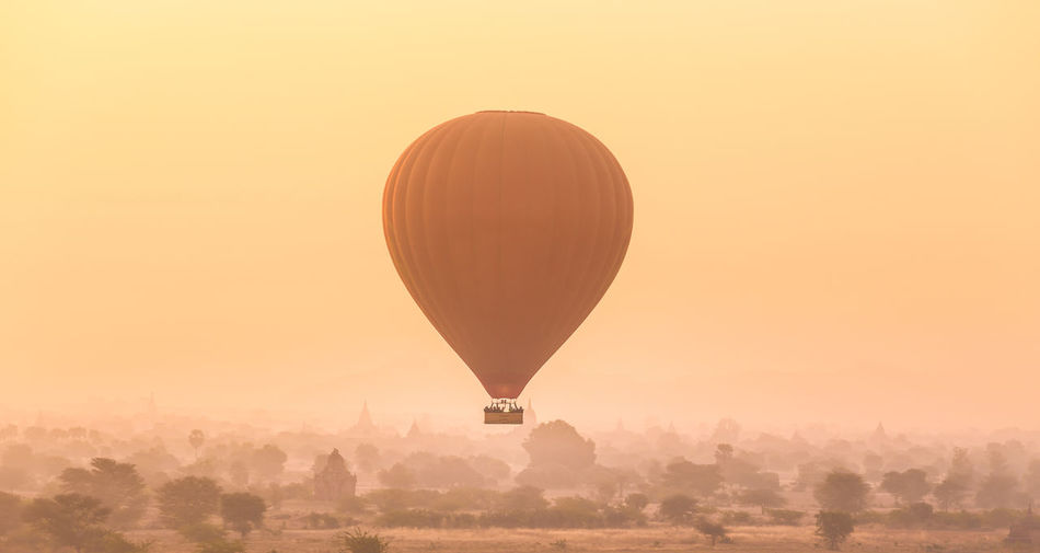 Hot air balloon flying over landscape against sky during sunset