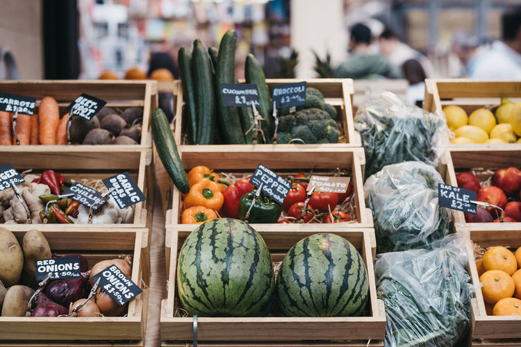 Variety of fresh fruit and vegetables in wooden crates, on sale at a market.