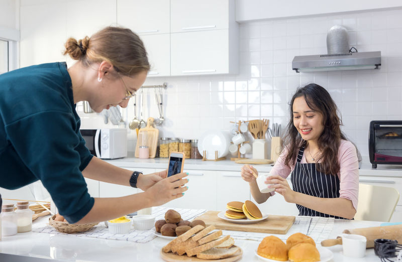 Young woman holding food on table at home