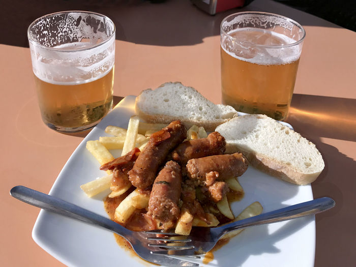Beer with tapas of sausage and fries Beer Beer - Alcohol Beer Glass Close-up Day Drink Drinking Glass Food Food And Drink Freshness Fries Meat No People Ready-to-eat Refreshment Sausage Serving Size Table Tapas Tortilla Tortilla Española