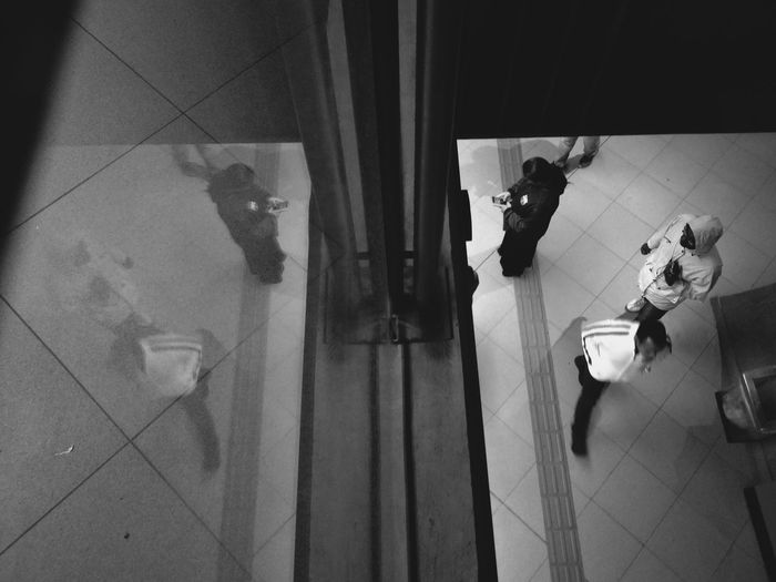Reflection of people on tiled floor