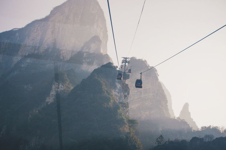 Low angle view of overhead cable cars against mountains