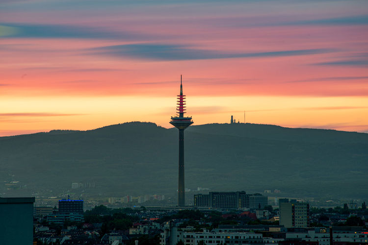 Communications tower in city against romantic sky at sunset