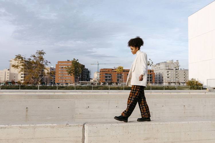 Full length of boy looking at city against sky