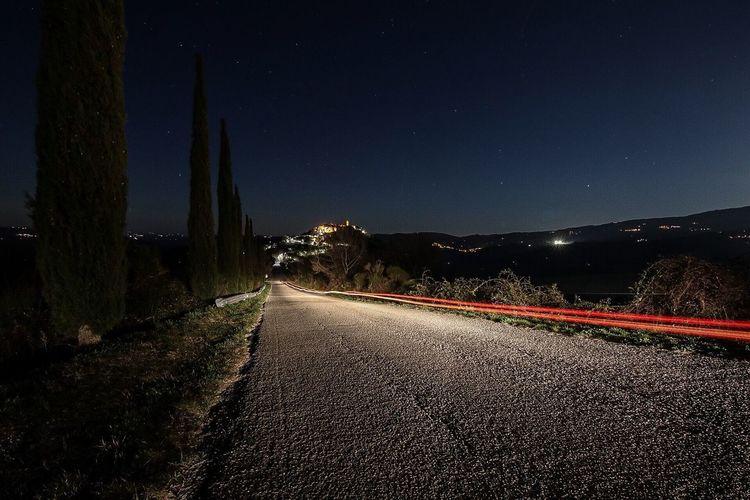 Empty road by illuminated city against sky at night
